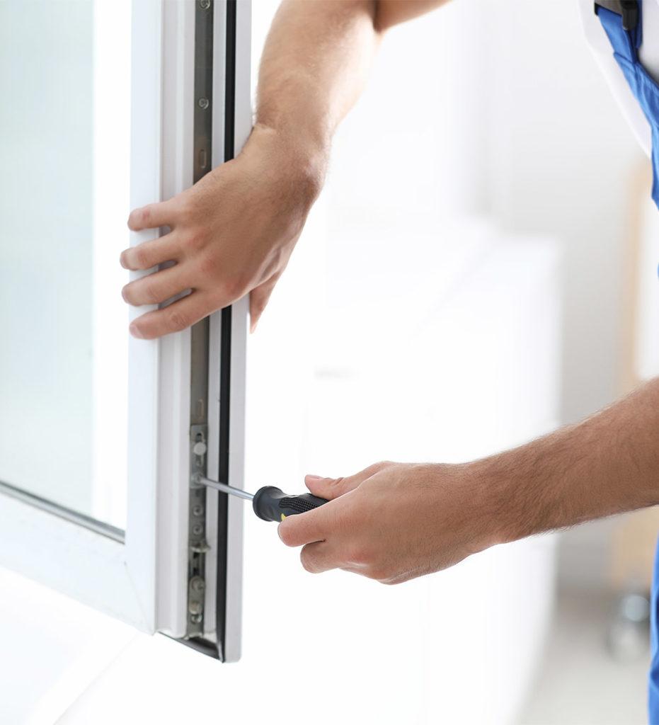 Bild von einem Fensterbauer der ein Fenster montiert